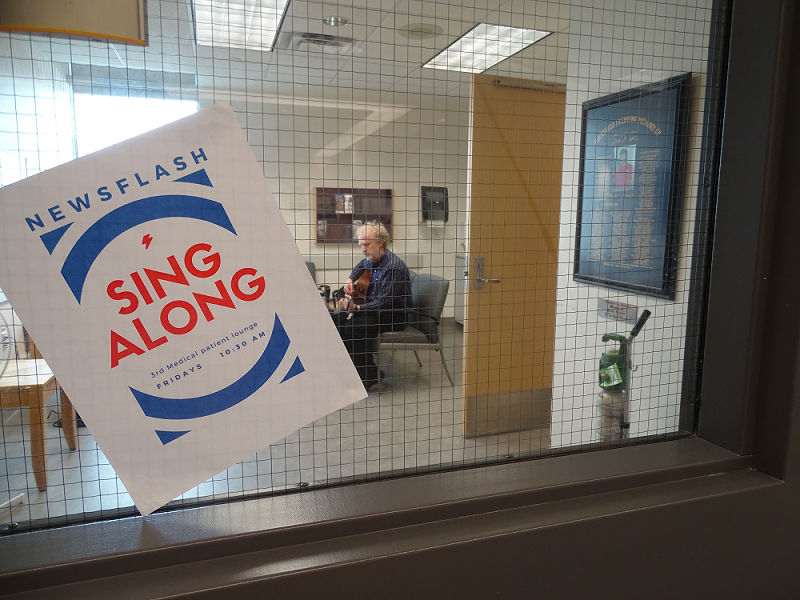 a sign that says Sing Along is taped on a window while you see a man playing a guitar in the background