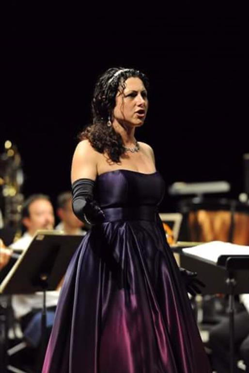 Female opera singer in purplse dress standing alone singing on a stage