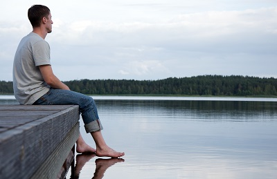 young man sitting on the edge of a dock looking out at calm water on a lake
